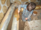"2013-12-28 : Our helper Gage applying some ""clay slip"" to the ductwork to give the cob more to stick too."