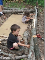The kids helping to pack in clay into the gaps between the logs