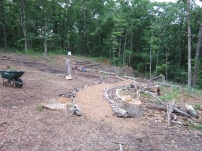 Laying out the stones to create a barefoot path, and a hugelkultur bed off to the right side of it to grow strawberries